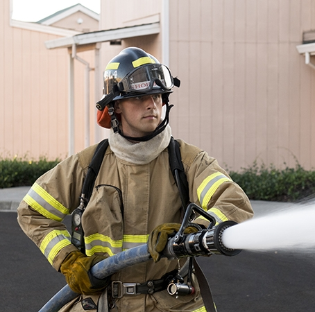 Firefighter demonstrates the use of a fire hose