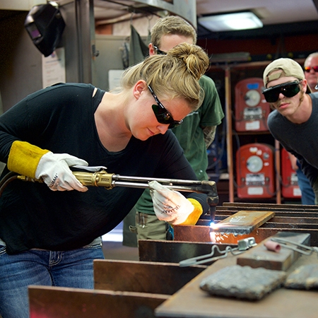 Lady welder uses acetylene torch as other students observe